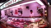 satıcı : BARCELONA, SPAIN - MAY 2017: Meat shop workers in the Boquer a market slice the product. Indoor shot. Stok Video