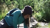 young woman tourist drink water, wets hands in a mountain river. Slider 50 fps