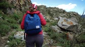 Young tourist woman in cap with backpack climbing stones mountains. Back view