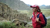Traveler girl in cap with backpack climbing stones mountains. Close-up view. Background mountains and river.