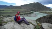 Young woman tourist is sitting on a stone and taking self photo on smartphone. Beautiful mountain and blue mountain river in the background Stok Video