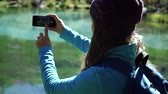 Young woman tourist is standing on a beautiful mountain lake and is enjoying scenic view in a sunny day. Traveler girl starts taking photos on smartphone Stok Video