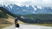 Young tourist woman hitchhiker is pulling a heavy backpack on a mountain road. There are snow mountains in the background. Stok Video