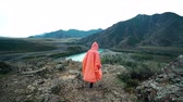 соло : Girl traveler in orange raincoat coming to the edge of the cliff in the mountains. Back view