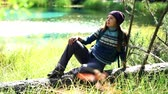 そのまま : Beautiful tourist woman with backpack in warm sweater and hat sits on a fallen tree by mountain lake. Front view