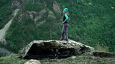 そのまま : Girl traveler in a vest and hat is standing on a big stone in the tree-covered mountains 動画素材