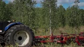 virgem : Tractor with driver silhouette in cabin hitched operates on spring filed near a birch forest Stock Footage