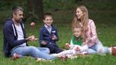 eating outside : Happy family playing outdoors in autumn park. Dolly shot. 4k. Slow motion.