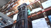 палетка : The driver on the forklift lifts the pallets with the box on the top shelf and leaves. 4K Slow Mo Стоковые видеозаписи