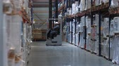 distribuidor : A forklift drives along huge stands with goods in a logistic warehouse. 4K Slow Mo Archivo de Video