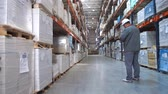 consignation : Logistics warehouse. The worker goes between the stands with the pack and makes notes. 4K Slow Mo