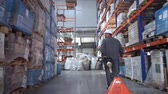 consignation : A man carries a lift for pallets in a logistic warehouse. 4K Slow Mo