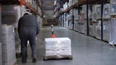 distribuidor : A man in a helmet and uniform packs a pallet. Logistics warehouse. 4K Slow Mo