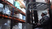 тележка : Logistics warehouse. A man moves in a special car, raises the goods on the shelf. 4K Slow Mo Стоковые видеозаписи