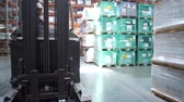 auditor : Warehouse with goods. The camera in motion, accompanied by a forklift. 4K Slow Mo