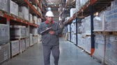 consignation : A warehouse worker in uniform walks along the racks, he holds a folder in his hands, he makes notes. 4K Slow Mo