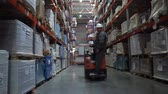 auditor : The worker rides along the row along the high racks with the products. 4K Slow Mo Stock Footage
