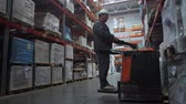consignation : Sort goods in a logistic warehouse. The worker puts the pallets with boxes. 4K Slow Mo Vidéos Libres De Droits