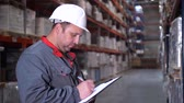 distribuidor : Close-up. The face of a warehouse worker. A man makes notes in his folder. 4K Slow Mo Vídeos