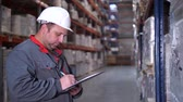 consignation : An employee at a logistics warehouse describes products. Close-up. 4K Slow Mo