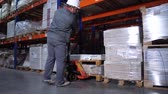 distribuidor : Warehouse worker puts pallets. A man works with a manual forklift. 4K Slow Mo