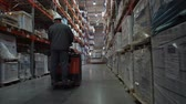 distribuidor : The worker rides on the square between the shelves filled with boxes of goods. 4K Slow Mo