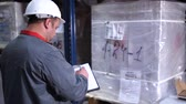 consignation : A warehouse worker in a helmet writes his note into his folder. 4K Slow Mo