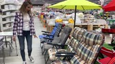 agd : Young woman in a huge supermarket chooses a lounge chair. 4K Slow Mo Wideo