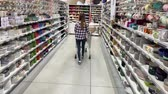 agd : A young woman with a trolley walks between the rows with dishes in a hypermarket. 4K Slow Mo