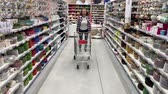 agd : Positive young woman have fun in the supermarket. The girl rides a cart. 4K Slow Mo Wideo