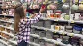 agd : A woman in a plaid shirt chooses a cup in the dishes section. Huge hypermarket. 4K Slow Mo