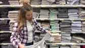 A woman takes a towel from a shelf, a young girl makes purchases in a hypermarket. 4K Slow Mo