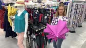 agd : Woman chooses an umbrella in the hypermarket. The girl takes a pink umbrella, opens it and spins under it. 4K Slow Mo Wideo