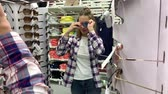 agd : Young woman trying on glasses in a hypermarket. Looks in the mirror and smiles. 4K Slow Mo