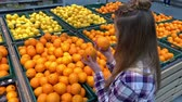 agd : Supermarket. The girl in the fruit department picks oranges. 4K Slow Mo