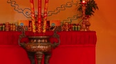 devoção : Nha Trang, Vietnam, Asia July 5 2018. Vietnamese temple table offerings fruits and drinks on a table top covered with a vibrant red table cloth and candles.