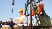 tube : Business woman write on clipboard in an oilfield, control work of the oil pump jack