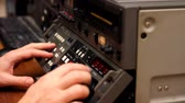 cimborák : Editor working on Betacam Sp recorder in Tv Studio, He turning and pushing shuttle and jog, and looking a footage on the tape Stock mozgókép