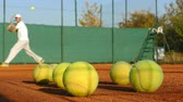 veterán : Man playing tennis on clay court, balls in front