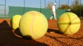 tenisz : Man playing tennis on clay court, balls in front