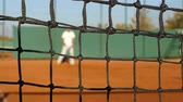 veterán : Man playing tennis on clay court, net in front, slow motion