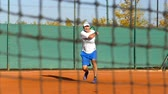 strike : Man playing tennis on clay court, net in front