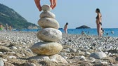 banho de sol : The child plays with stones balance on beach, people sunbathe, swim and enjoy on sea vacation