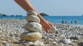 stabilita : The child plays with stones balance on beach, people sunbathe, swim and enjoy on sea vacation