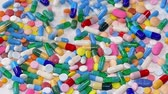 pharmaceutics : Colorful pills and drugs falling on white table, concept of medical treatment, slow motion