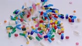 szintetikus : Colorful pills and drugs falling on white table, concept of medical treatment, slow motion