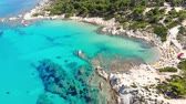 banho de sol : Aerial view of beautiful sandy and rocky Orange beach, people sunbathing and swimming. Drone shot flying over amazing famous Orange also called Portokali beach on Sithonia near Sarti, Greece