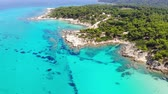 suntan : Aerial view of beautiful sandy and rocky Orange beach, people sunbathing and swimming. Drone shot flying over amazing famous Orange also called Portokali beach on Sithonia near Sarti, Greece