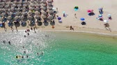 Aerial view of beautiful sandy beach, people sunbathing and swimming. Drone shot flying over Kalamitsi beach in Sithonia, Greece Vídeos