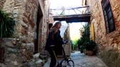 mountainbiken : A girl with long hair walks with a bicycle in the small stone medieval village. Picturesque countryside. Rural bike ride. Old stone street. Golden light. Videos
